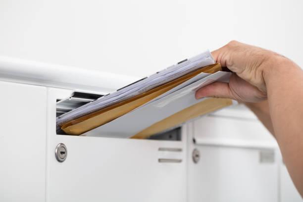 menschen nehmen briefe aus postfach - gefüllte bon bons stock-fotos und bilder