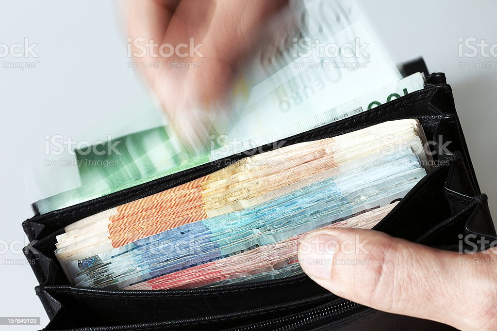 Man Taking Money out of Full Wallet royalty-free stock photo