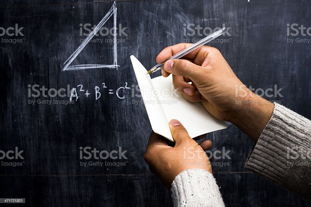 Man taking notes of math theorem on blackboard royalty-free stock photo
