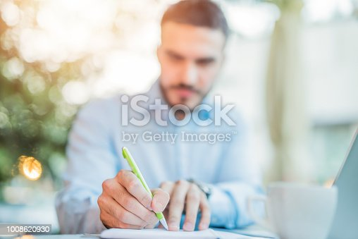 Man taking notes outdoors in coffee shop.