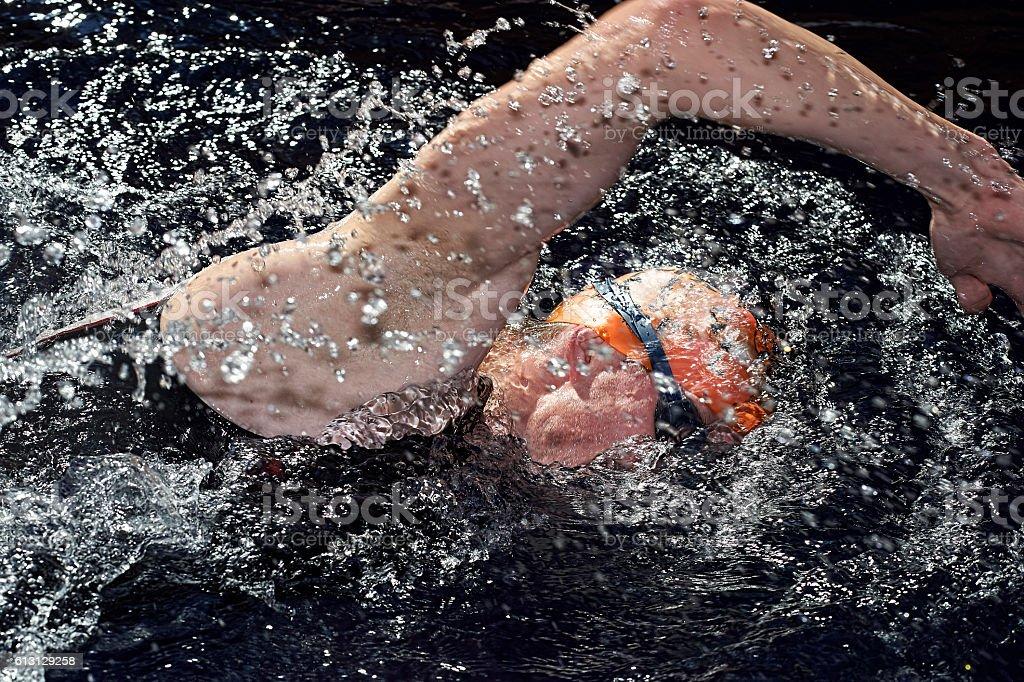 Man taking part in amateur triathlon at swimming pool stock photo