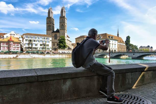 menschen nehmen foto am limmatquai und grossmünster kirche in zürich - senior bilder wasser stock-fotos und bilder