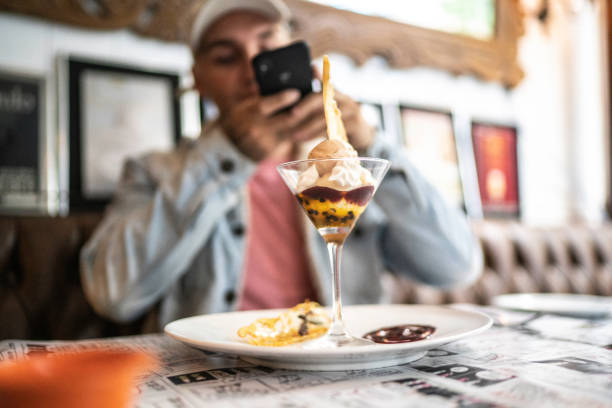 man taking photo of a dessert - foodie stock photos and pictures