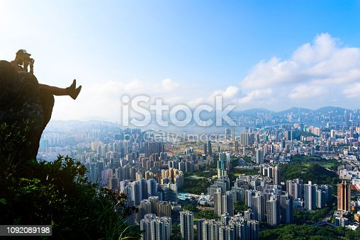 Man taking photo of a Hong Kong cityscape view from the Lion rock