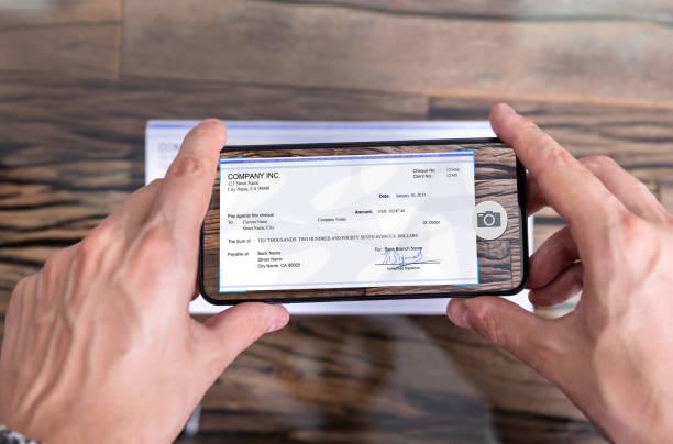 uomo che scatta foto di assegno per effettuare un deposito remoto - dispositivo informatico portatile foto e immagini stock