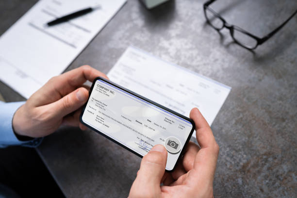 Man Taking Photo Of Cheque To Make Remote Deposit Man Taking Photo Of Cheque To Make Remote Deposit In Bank bank deposit slip stock pictures, royalty-free photos & images