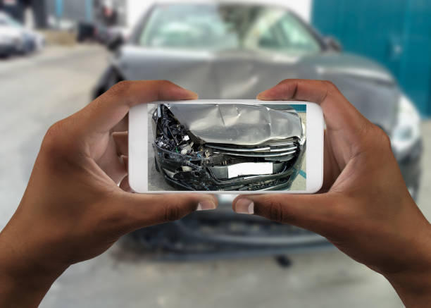 Man taking photo of his car with damages stock photo