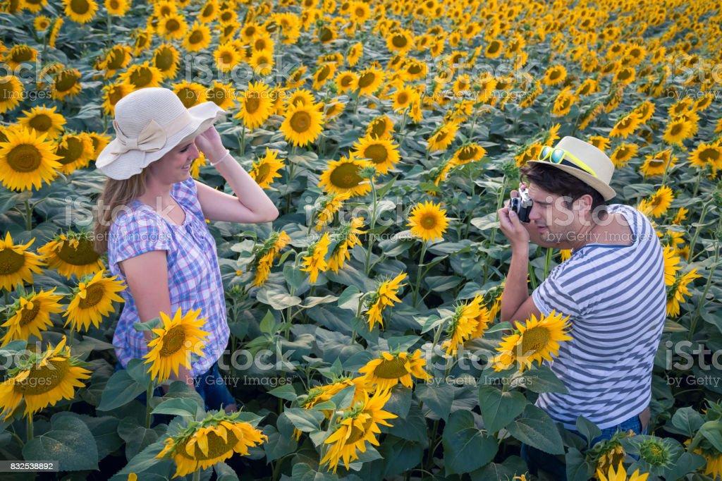 Man taking photo of his girlfriend in sunflower field