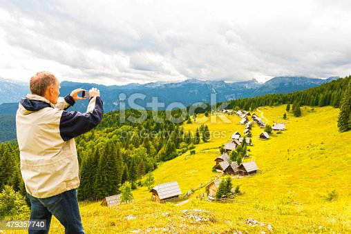 Mature man in sport jacket taking photo with mobile phone of line of mountain huts in the scenic pastureland. Some spruce trees around and mountain range in background.