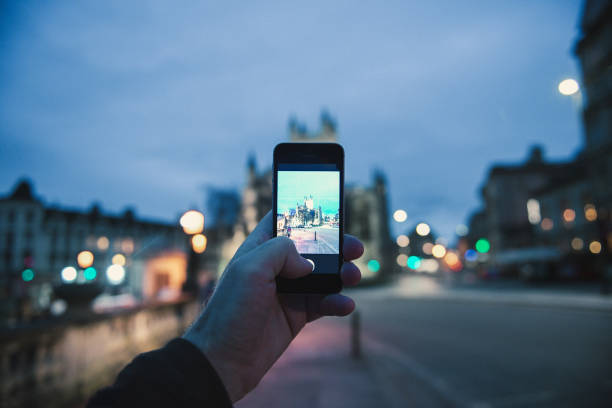 man taking photo on smartphone mobile phone of the Bath Cathedral in united kingdom Bath: Personal Perspective pov of man taking photograph with the mobile phone smartphone of the illuminated cathedral Bath Abbey in Bath, United Kingdom bath abbey stock pictures, royalty-free photos & images