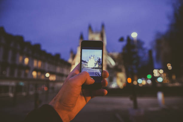 man taking photo on smartphone mobile phone of the Bath Cathedral in united kingdom Bath: Point of view of man taking photograph with the mobile phone smartphone of the illuminated cathedral Bath Abbey in Bath, United Kingdom bath abbey stock pictures, royalty-free photos & images