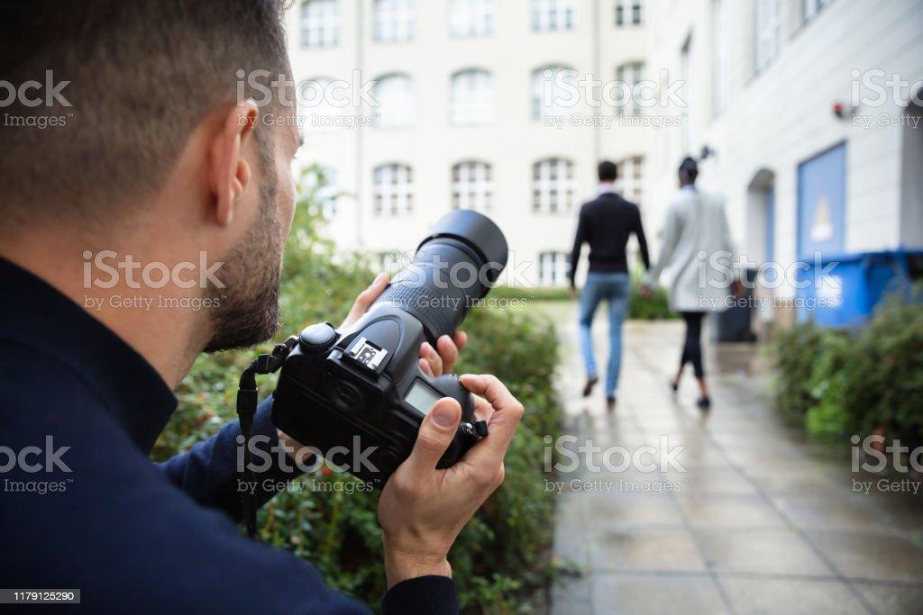 Mann, der Foto von Paar zu Fuß zusammen im Freien - Lizenzfrei Argwohn Stock-Foto