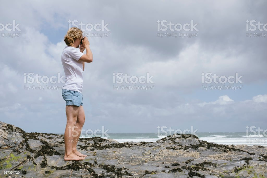 Man taking photograph with old film camera, Towan Beach, Newquay, Cornwall stock photo
