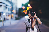 A young Japanese man is taking photos at night in Tokyo.