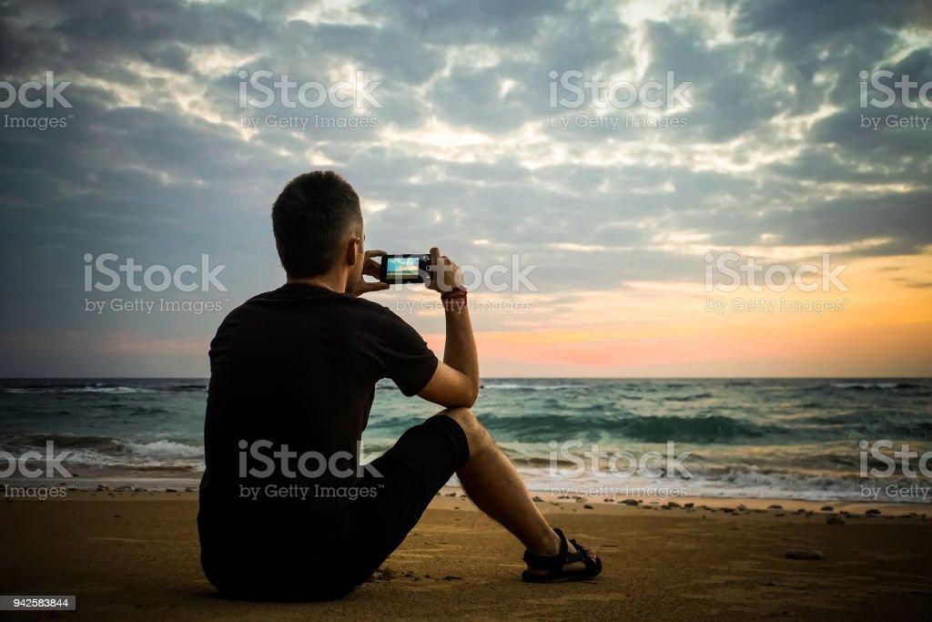 Mann die Fotos von Sonnenuntergang mit Handy – Foto