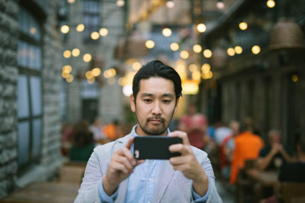 man taking photos with smartphone - photo messaging stock photos and pictures