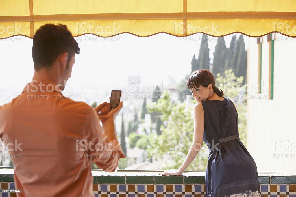 Man taking picture of girlfriend on balcony royalty free stockfoto