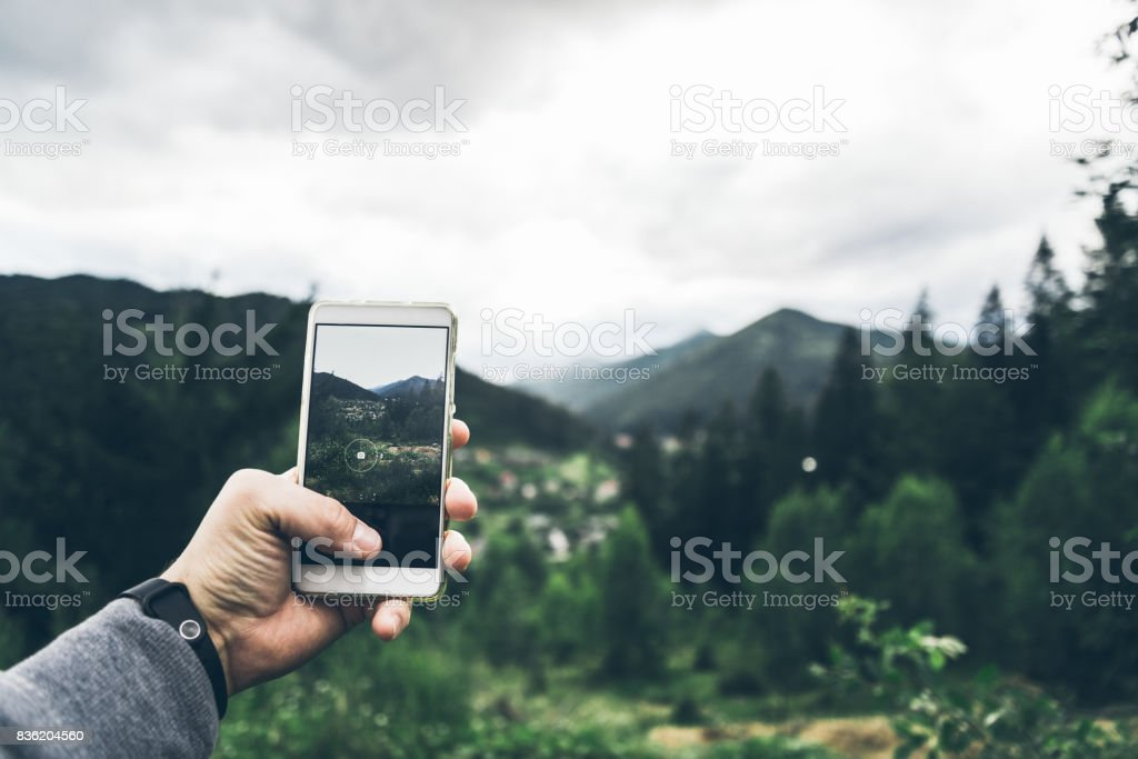 man taking picture of the mountains on his phone stock photo