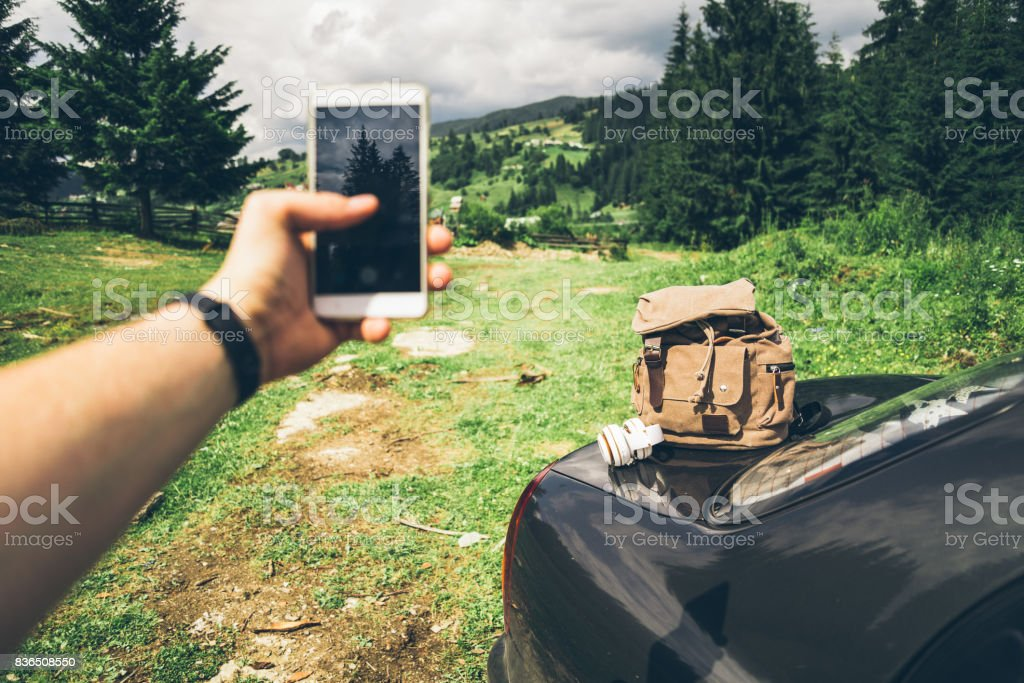 man taking picture on his phone in mountains stock photo