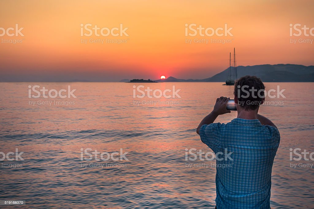 Man taking picture with mobile telephone at sunset, Croatia. royalty-free stock photo