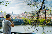 Man taking pictures of Vltava river during day Castle of Prague in background with Charles Bridge
