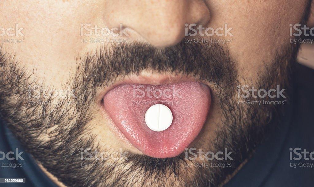 Tomar la píldora hombre, tableta de fármacos o medicamentos en lengua con la boca abierta. Tratamiento analgésico o droga de fiesta - foto de stock