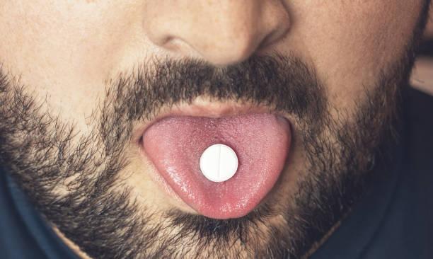 man nemen pil, tablet van drugs of medicijnen op tong met open mond. pijnstiller behandeling of partij verdovende middelen - amfetamine stockfoto's en -beelden