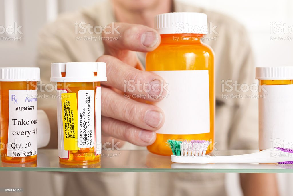 Man taking pills out of medicine cabinet stock photo