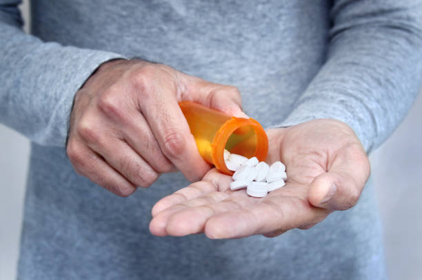 man taking pills - prescription stock photos and pictures