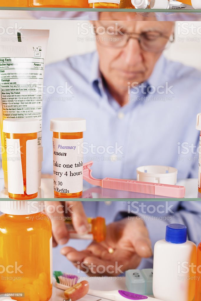 Man taking prescription pills out of medicine cabinet. Bottles, toiletries. stock photo