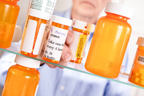 Man taking prescription pills out of medicine cabinet stock photo