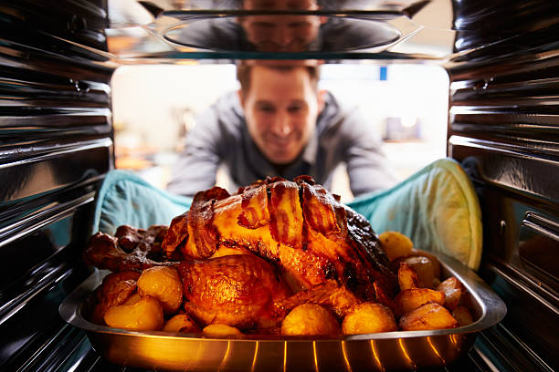 man taking roast turkey out of the oven - gebraden vlees stockfoto's en -beelden