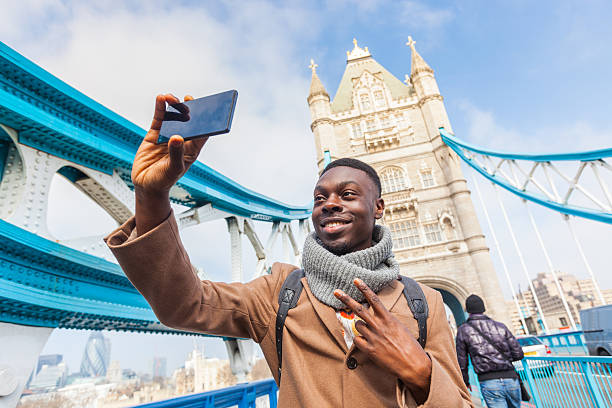 Man taking selfie in London with Tower Bridge on background stock photo