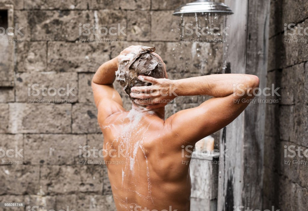 Man taking shower and washing hair stock photo