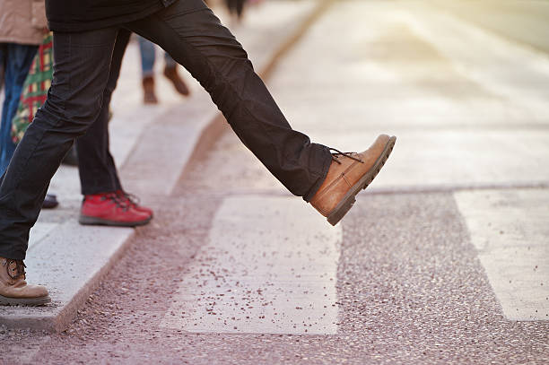 Man taking the step (onto zebra crossing) Man taking the step (onto zebra crossing) single step stock pictures, royalty-free photos & images