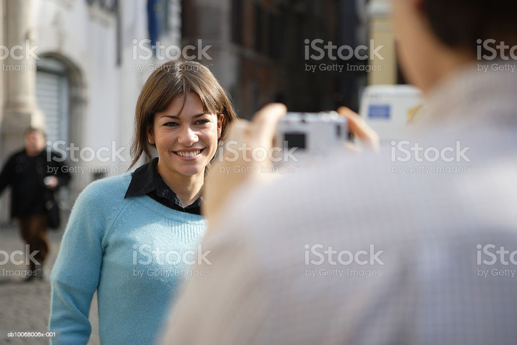 Man taking woman's pictures on street royalty-free stock photo