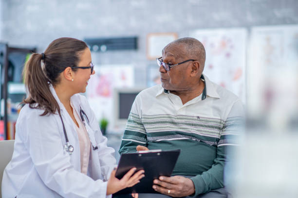 man talking advice from a doctor. - elderly patients stock photos and pictures