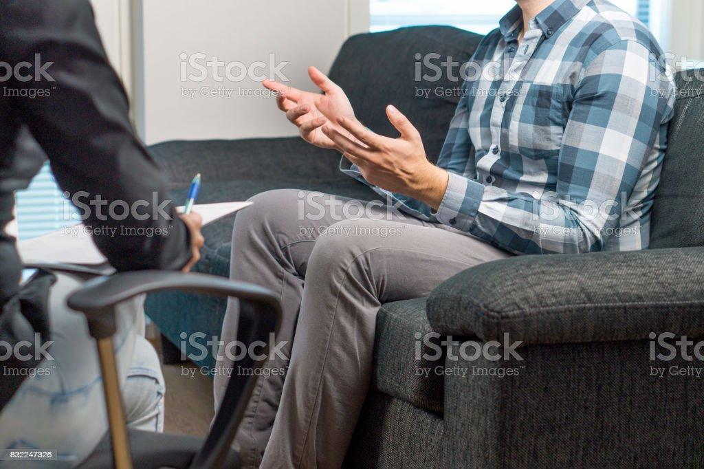Hombre hablando y agitando las manos en la sesión de terapia con psiquiatra, psicólogo, consejero, terapeuta o vida de entrenador. Reunión con profesionales especializados con un bloc de notas. Paciente masculino sentado en el sofá. - foto de stock