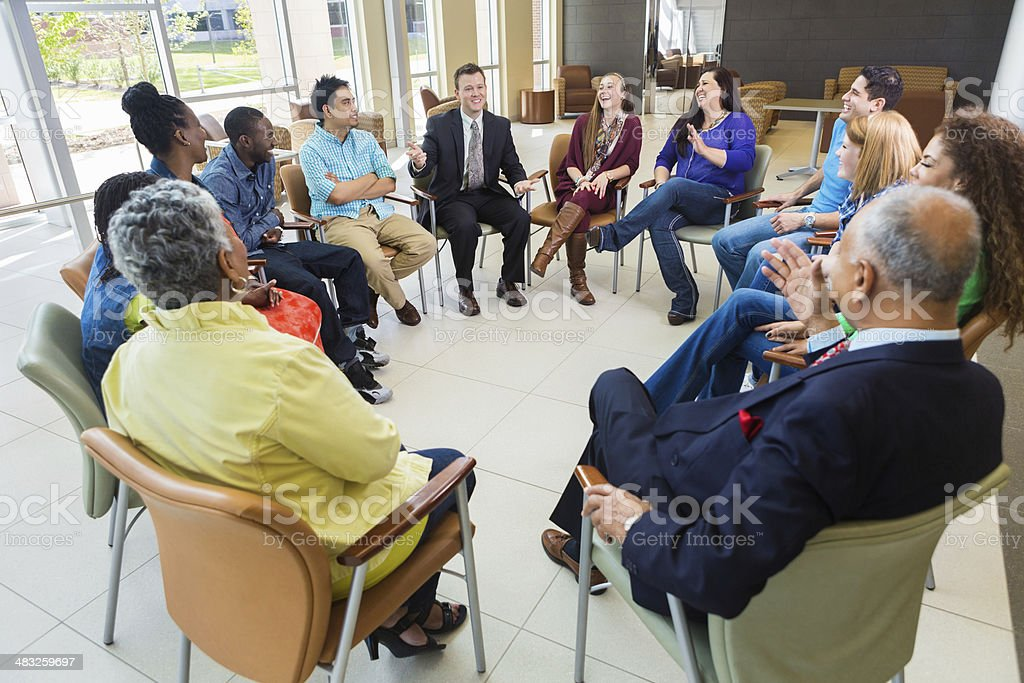 Man talking in light-hearted discussion group stock photo