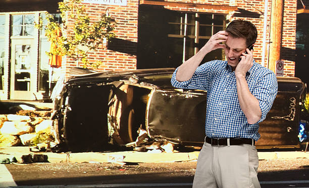 Man talking on mobile phone after car accident stock photo