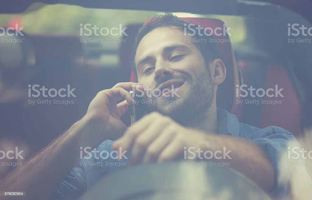 man talking on mobile phone while driving his car stock photo