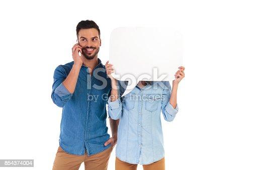 854381780istockphoto man talking on phone, woman holds speech bubble over face 854374004