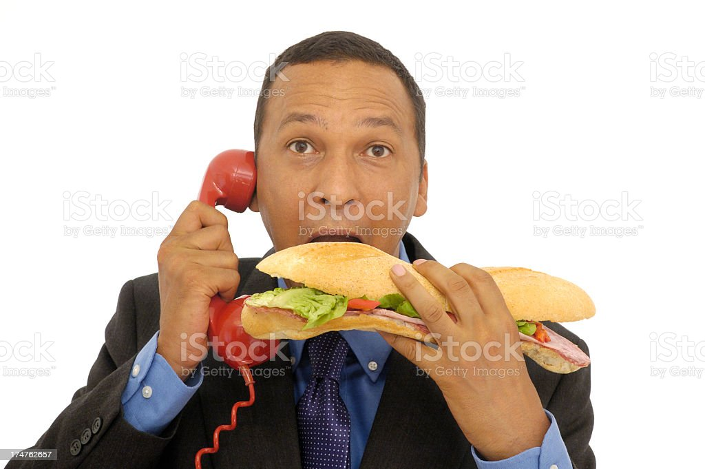 Man talking on telephone simultaneously biting footlong sub royalty-free stock photo