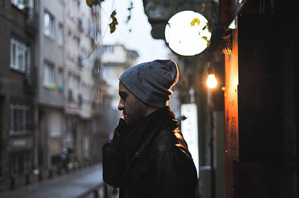 Man talking on the phone in a narrow street stock photo