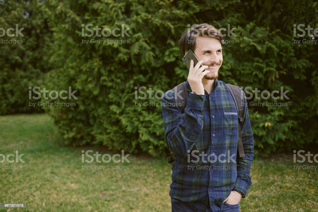 Man talking on the phone in the park,  green background stock photo