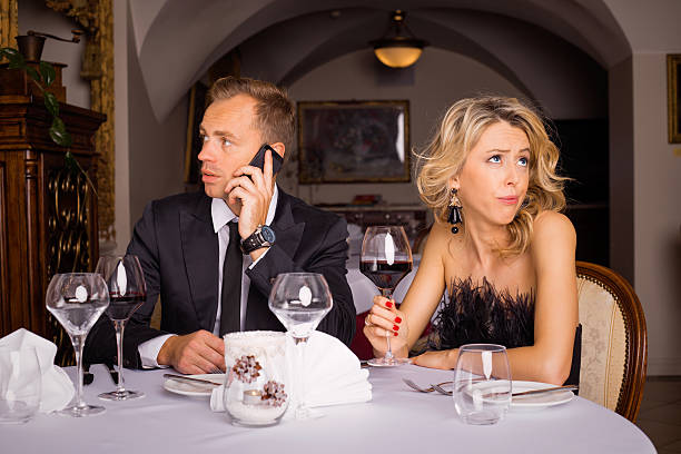 Man talking on the phone while he is on date Man talking on the phone while he is on date bad date stock pictures, royalty-free photos & images