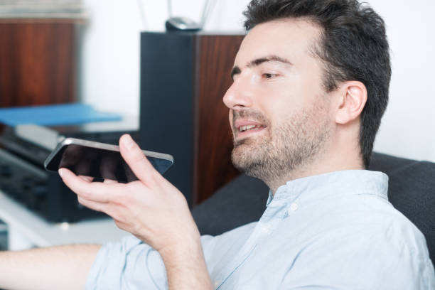 Man talking on the phone with the digital voice assistant stock photo
