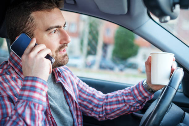 man talking on the smartphone and driving a car - detraction stock pictures, royalty-free photos & images