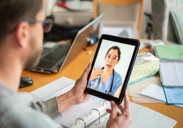 Man talking online with his doctor using a digital tablet stock photo