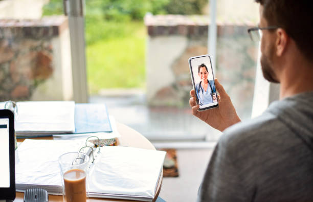 Man talking online with his doctor using a smart phone stock photo